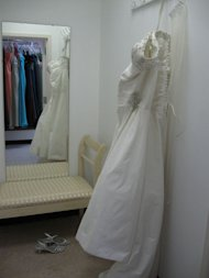 wedding dress hanging in fitting room