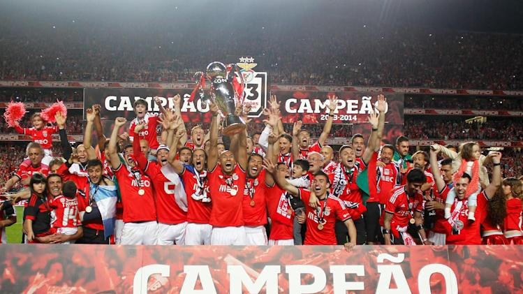 Benfica's team captain Luisao, from Brazil, lifts the trophy at the end of their Portuguese league soccer match with Olhanense on Sunday April 20, 2014, at Benfica's Luz stadium in Lisbon. Benfica defeated Olhanense 2-0 to win the championship with two rounds left to play