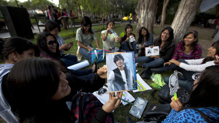 In this May 11, 2013 photo, a fan of South Korean singer Hyun Joong shows her picture of him as she sits with other fans as they celebrate the singer's birthday in Ramon Castilla park in Lima, Peru. Hundreds of fans of K-pop gather each week in the downtown park to dance to the energetic music. Some dress up as Korean comic book characters. (AP Photo/Martin Mejia)