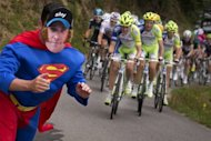 A fan dressed as Superman with a mask representing overall leader British Bradley Wiggins, poses as the pack rides in the seventeenth stage of the 2012 Tour de France cycling race starting in Bagneres-de-Luchon and finishing in the ski resort of Peyragudes, southern France