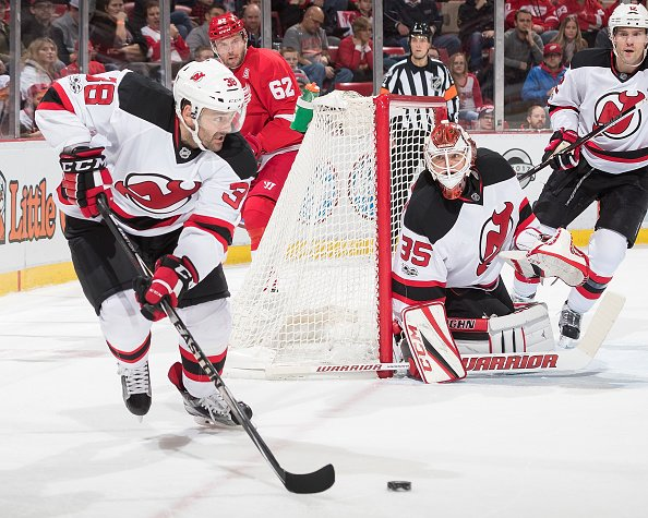 DETROIT, MI - JANUARY 31: Vernon Fiddler #38 of the New Jersey Devils skates around the net with the puck in front of Thomas Vanek #62 of the Detroit Red Wings during an NHL game at Joe Louis Arena on January 31, 2017 in Detroit, Michigan. The Devils defeated the Wings 4-3. (Photo by Dave Reginek/NHLI via Getty Images)