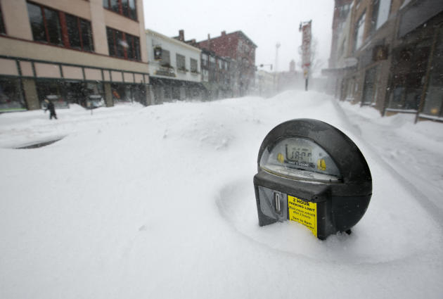 A parking meter pokes out of a snow bank during a blizzard, Saturday, Feb. 9, 2013, in Portland, Maine. The storm dumped more than 30 inches of snow as of Saturday afternoon, breaking the record for t