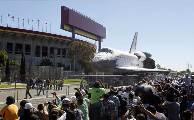 The space shuttle Endeavour moves north on Bill Robertson Lane in front of the Coliseum in Los Angeles Sunday, Oct. 14, 2012. In thousands of Earth orbits, the space shuttle Endeavour traveled 123 mil