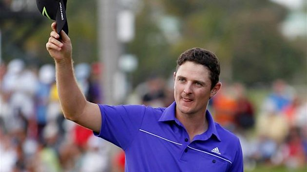 Britian's Justin Rose reacts after sinking his final putt on the 18th green during fourth round play in the WGC-Cadillac Championship PGA golf tournament at the Doral Golf Resort in Doral, Florida, March 11, 2012