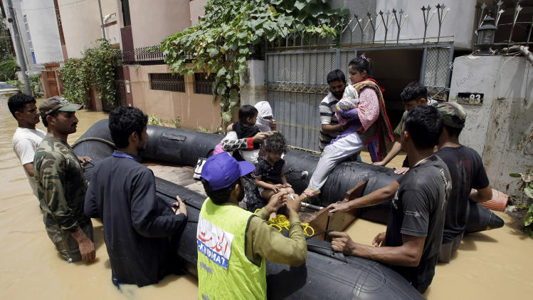 Pakistani soldiers rescue a family from an area flooded by heavy rains on the outskirts of Karachi, Pakistan, Sunday, Aug. 4, 2013. Heavy rains that swept across Pakistan brought down more than 100 homes and caved in a factory wall, killing at least a dozen people in the downpours, officials said. (AP Photo/Fareed Khan)