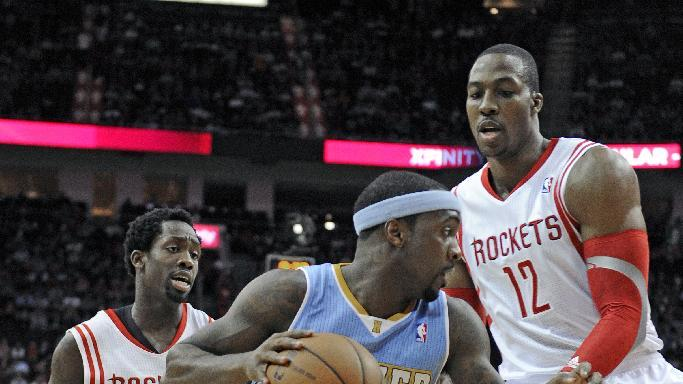Denver Nuggets' Ty Lawson, center, drives the ball between Houston Rockets Patrick Beverley (2) and Dwight Howard (12) in the first half of an NBA basketball game Saturday, Nov. 16, 2013, in Houston