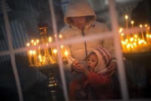 A boy is helped by his mother to light a candle inside…