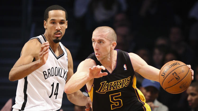Los Angeles Lakers point guard Steve Blake (5) drives around Brooklyn Nets point guard Shaun Livingston (14) in the first quarter of an NBA basketball game at the Barclays Center, Wednesday, Nov. 27, 2013, in New York