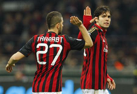 AC Milan's Kaka high fives Adel Taarabt during their Champions League round of 16 first leg soccer match against Atletico Madrid at the San Siro stadium in Milan