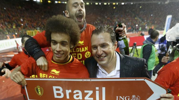 Belgium's soccer team coach Wilmots and player Witsel celebrate with champagne after a 2014 World Cup qualifying soccer match against Wales in Brussels