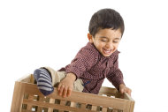 boy climbing out of box