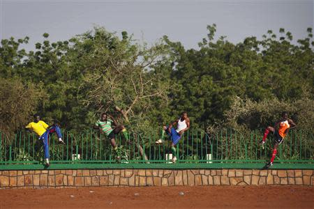 Soccer players, perched on a fence, watch a pick-up game in Niamey