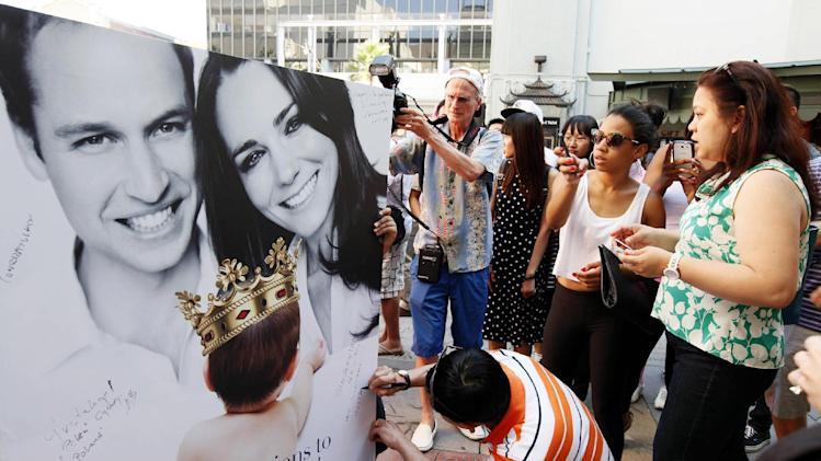 Fans and tourists sign a giant card congratulating Britain's Prince William and Kate, Duchess of Cambridge, on the birth of their baby boy Tuesday, July 23, 2013 outside the TCL Chinese Theatre in the Hollywood district of Los Angeles in Los Angeles Tuesday, July 23, 2013. (AP Photo/Nick Ut)