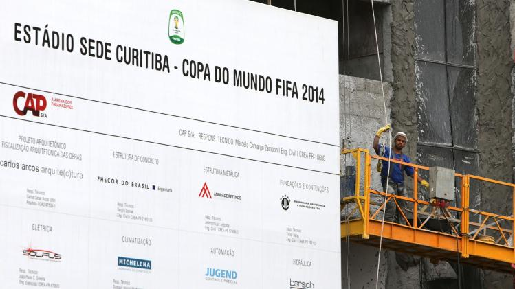 A worker stands on a scaffolding on the exterior of the Arena da Baixada soccer stadium as it is being built to host matches of the 2014 World Cup in Curitiba