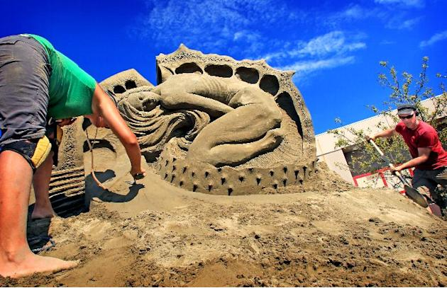 In this Aug. 28, 2011 photo, Susanne Ruesler from the Netherlands, left, and Fergus Mulvany from Dublin, Ireland, put the finishing touches on their sand sculpture called A Beautiful Malady during the