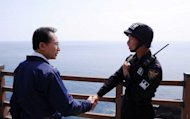 South Korean President Lee Myung-Bak shakes hands with a police guard during a visit to remote islands disputed with Japan, known as Dokdo in Korea and Takeshima in Japan. Lee has paid a surprise visit to islands at the centre of a decades-long territorial dispute with Japan, which recalled its ambassador from Seoul in protest