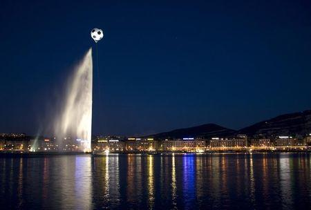 A giant helium-inflated soccer ball flies over the jet d'eau, or water fountain, at the Lac Leman in Geneva