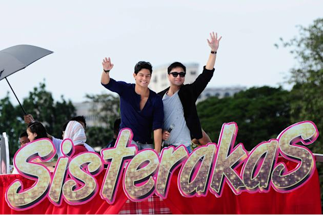 "Daniel Matsunaga and DJ Durano wave to fans as the float of the MMFF 2012 entry ""Sisterekas"" makes its way through the crowd during the 2012 Metro Manila Film Festival Parade of Stars on 23 December 2"