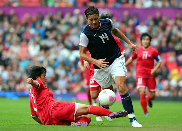 Abby Wambach of United States is tackled by Kim Myong Gum of DPR Korea during the Women's Football first round Group G match between the United States...