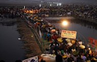 Indian Hindu devotees cross a bamboo bridge as they gather to pay homage to the setting sun during the Chhat Puja festival on the banks of the Ganges River in Patna. At least 18 women and children were killed and more than a dozen people seriously hurt in a stampede after the bridge collapsed