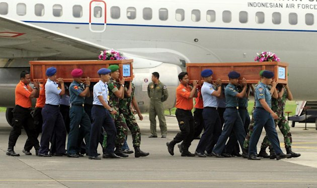 Indonesian soldiers carry coffins containing bodies of victims of AirAsia Flight 8501 upon arrival at Indonesian Military Air Force base in Surabaya, Indonesia, Wednesday, Dec. 31, 2014. A massive hunt for the victims of the jet resumed in the Java Sea on Wednesday, but wind, strong currents and high surf hampered recovery efforts as distraught family members anxiously waited to identify their loved ones. (AP Photo/Firdia Lisnawati)