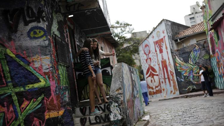"Women take a selfie with a mobile phone between graffiti-filled walls along ""Beco do Batman"" (Batman's alley) in the Vila Madalena neighbourhood, which is a well-known open-air graffiti museum, in Sao Paulo"