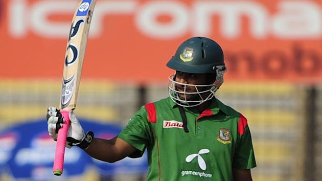 Bangladeshi cricketer Tamim Iqbal raises his bat after scoring a half century