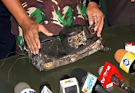 An Indonesian military officer displays the charred black box of the Russian Sukhoi Superjet 100, Russia's first post-Soviet civilian aircraft, at the search and rescue base in Cijeruk near Mount Salak