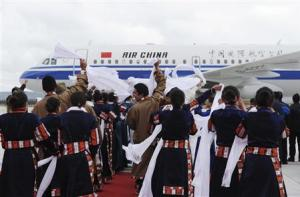 Local Tibetans wave traditional silk scarves as they greet the first group of passengers who landed at Daocheng Yading Airport in Garze Tibetan Autonomous Prefecture