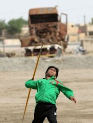 Iraqi Paralympian Ahmed Naas throws his javelin at an open field in Batha. Lacking the money for exercise equipment, Naas works out on the roof of his family's home with a small weighted ball gifted to him by a coach and trains at a tract of dirt between a railway track and a main road