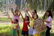 Children hold up placards on a street in Cagayan de Oro, on December 24. Thousands of people in the southern Philippines are spending Christmas in emergency shelters after floods that left more than 1,000 people dead and another 1,000 unaccounted for