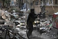A rebel fighter fires his weapon as he stands amidst rubble and debris during clashes with Syrian government forces in the northeastern city of Deir Ezzor, on November 11, 2013
