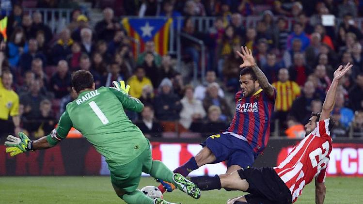 FC Barcelona's Daniel Alves, from Brazil, center, duels for the ball against Athletic Bilbao's goalkeeper Gorka Iraizoz, left, and Mikel Balenziaga, right, during a Spanish La Liga soccer match at the Camp Nou stadium in Barcelona, Spain, Sunday April 20, 2014
