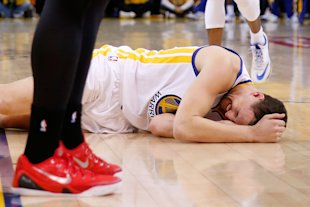 Klay Thompson lays on the court after being kneed in the head. (Ezra Shaw/Getty Images)