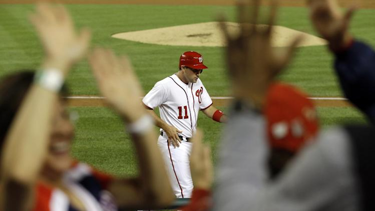 Fans cheer and high five as Washington Nationals Ryan Zimmerman (11) returns to the dugout after scoring against the Los Angeles Dodgers on a wild pitch during the third inning of a baseball game at Nationals Park, in Washington, on Thursday, Sept. 20, 2012. (AP Photo/Jacquelyn Martin)