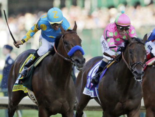 Victor Espinoza, left, rides American Pharoah to victory in the Kentucky Derby. (AP)