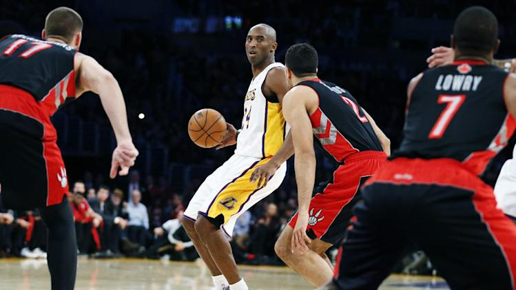 Los Angeles Lakers' Kobe Bryant dribbles the ball as he is guarded by Toronto Raptors' Landry Fields, second right, during the first quarter of an NBA basketball game in Los Angeles, Sunday, Dec. 8, 2013