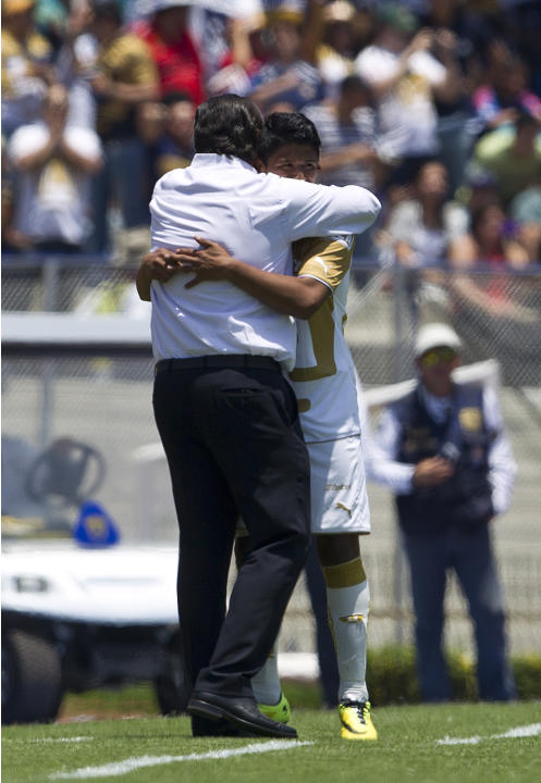 Pumas' Daniel Ramirez, right, celebrates after scoring against Chivas with coach Jose Luis Trejo during a Mexican soccer league match in Mexico City, Sunday, April  20, 2014