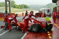 Ferrari F1 team members help Spanish driver Fernando Alonso into the pits of the Mugello track, during the fist day of the F1 official test session. Fernando Alonso's Ferrari overcame heavy rain which eventually triggered a premature end to the session to top the times at Tuesday's testing at Mugello