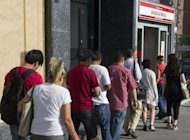 People wait in line at a government employment office in the center of Madrid in June. Spain's jobless rate neared 25 percent in June, officials said, darkening the recession outlook despite relief on financial markets at a vow of support by the European Central Bank