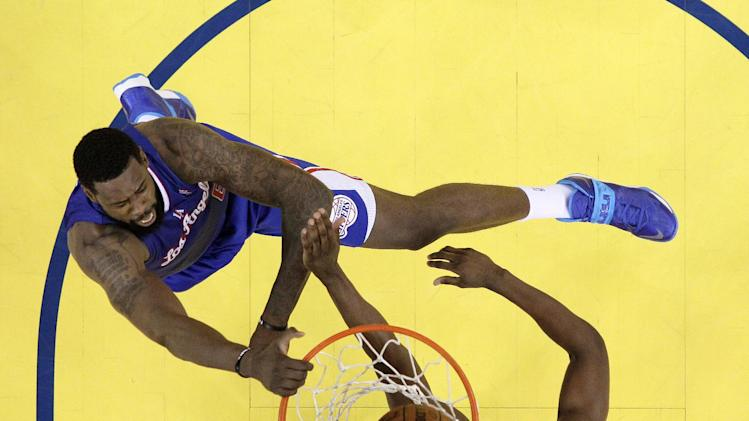 CORRECTS BYLINE - Los Angeles Clippers' DeAndre Jordan, top, dunks over Golden State Warriors' Harrison Barnes during the first half in Game 3 of an opening-round NBA basketball playoff series on Thursday, April 24, 2014, in Oakland, Calif. Los Angeles won 98-96