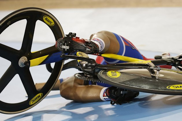 Cuba's Lisandra Guerra slides down the track after falling during the women's sprint quarterfinal track cycling competition at the Pan Am Games in Milton, Ontario, Saturday, July 18, 2015. (AP Photo/Felipe Dana)