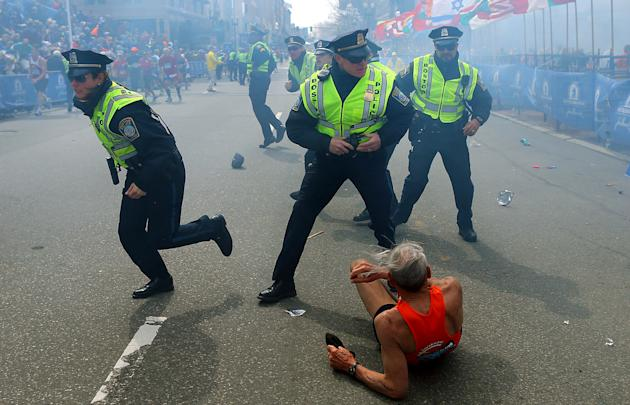 Bill Iffrig, 78, lies on the ground as police officers react to a second explosion at the finish line of the Boston Marathon in Boston, Monday, April 15, 2013. Iffrig, of Lake Stevens, Wash., was runn