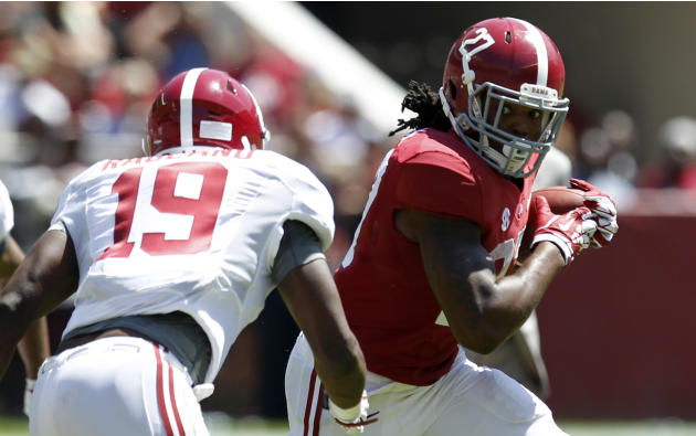 Alabama running back Derrick Henry (27) caries the ball as Alabama linebacker Reggie Ragland (19) closes in during Alabama's A-Day NCAA college football spring game Saturday, April 19, 2014, in Tu