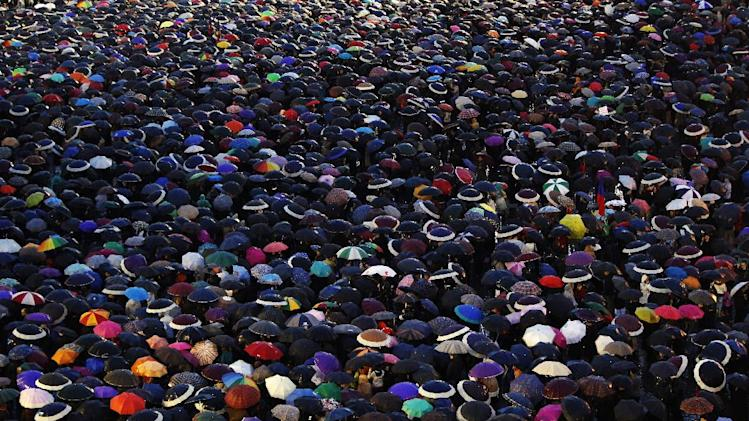 Visitors cover St. Peter's Square with their umbrellas as they wait for the election of a new pope by the cardinals in conclave in the Sistine Chapel at the Vatican, Wednesday, March 13, 2013.(AP Photo/Andrew Medichini)