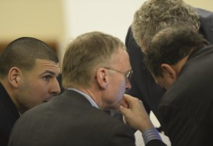 Aaron Hernandez (L) talks with his attorneys during his murder trial. (REUTERS)