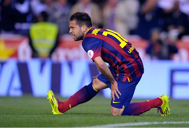 Barcelona's Jordi Alba grimaces while holding his leg during the final of the Copa del Rey between FC Barcelona and Real Madrid at the Mestalla stadium in Valencia, Spain, Wednesday, April 16, 201