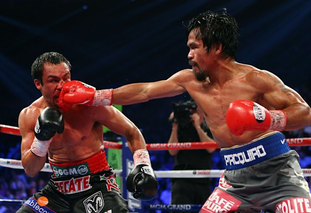 LAS VEGAS, NV - DECEMBER 08: (R-L) Manny Pacquiao throws a right at Juan Manuel Marquez during their welterweight bout at the MGM Grand Garden Arena on December 8, 2012 in Las Vegas, Nevada. (Photo by Al Bello/Getty Images)