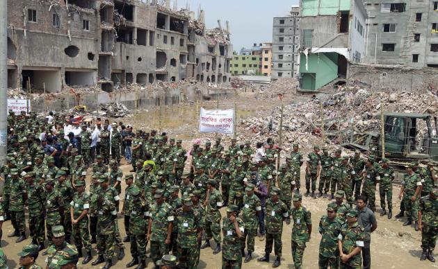 Bangladesh army soldiers and others gather at the wreckage of a Bangladeshi garment factory building to offer prayers for the souls of the 1,127 people who died in the structure's collapse last month,