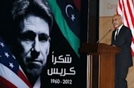 "Mohamed al-Megaryef, president of Libya's ruling national assembly, speaks during a ceremony to honor the late US Ambassador to Libya Christopher Stevens in Tripoli. The sign reads, ""Thanks Chris""."